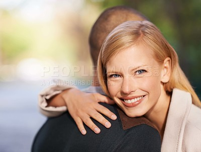 Buy stock photo Shot of a young woman embracing her boyfriend in the outdoors