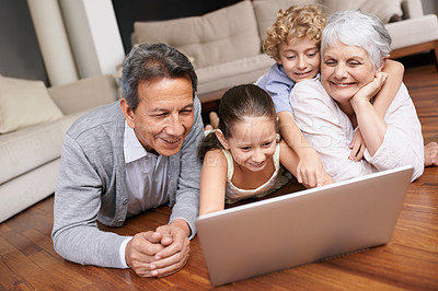 Buy stock photo Shot of grandchildren showing their grandparents something on a computer