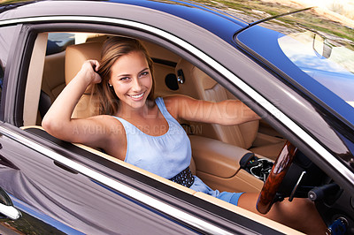 Buy stock photo Shot of a young woman driving in a sports car