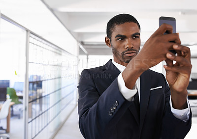 Buy stock photo A smiling businessman taking a picture with his cellphone