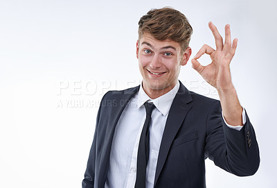 Buy stock photo Studio shot of a smiling businessman holding up an O.K. sign