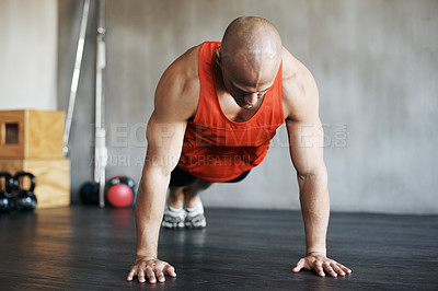 Buy stock photo Shot of a man doing pushups at the gym