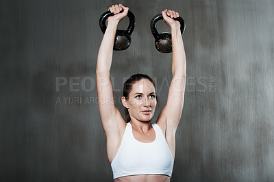 Buy stock photo Shot of a woman working out with kettle bells at the gym