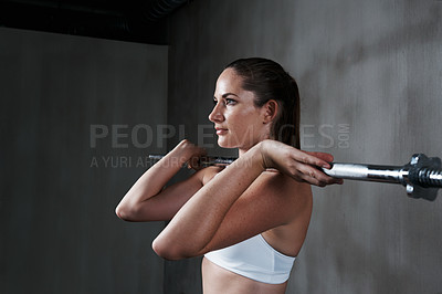 Buy stock photo Shot of a woman working out with a barbell at the gym