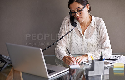 Buy stock photo Shot of a beautiful young businesswoman working at her desk