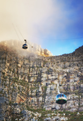 Buy stock photo A shot of two cable cars moving up and down the mountainside at Table Mountain, Cape Town.