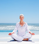 Relaxed mature old woman meditating on the beach