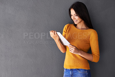 Buy stock photo Shot of an attractive young woman using a digital tablet
