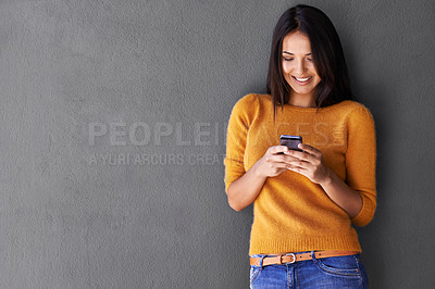 Buy stock photo An attractive young woman using a mobile phone while standing against a gray wall
