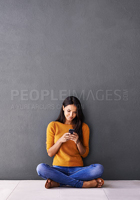 Buy stock photo Shot of an attractive young woman sitting on the floor with her mobile phone