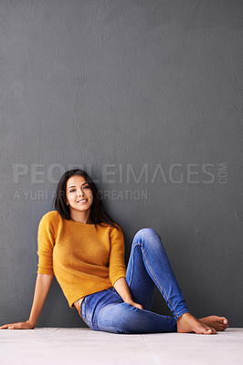 Buy stock photo Portrait of an attractive young woman sitting against a grey wall