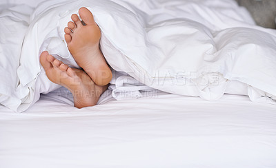 Buy stock photo A young woman's feet sticking out from underneath her duvet