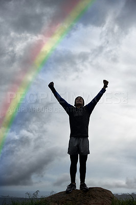 Buy stock photo A young man celebrating at the top of a mountain under a rainbow