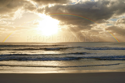 Buy stock photo Shot of a rainbow over a beautiful ocean