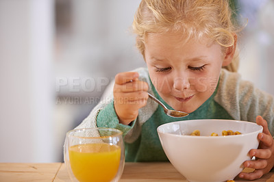 Buy stock photo Shot of a cute little girl eating breakfast at home