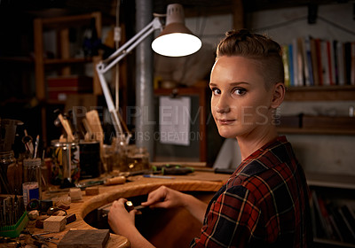 Buy stock photo Shot of a beautiful young woman sitting in a workshop