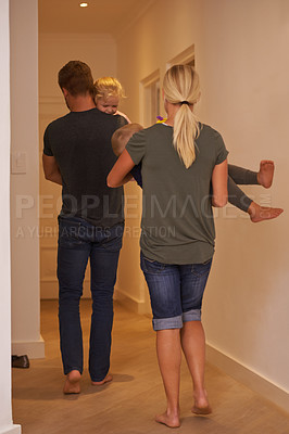 Buy stock photo Shot of young parents carrying their sleepy children to bed