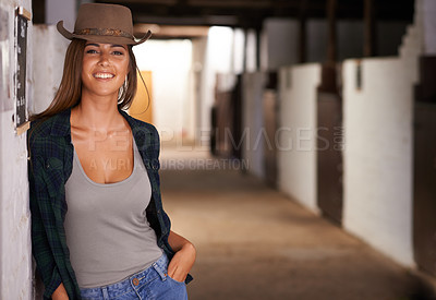 Buy stock photo A portrait of a beautiful young cowgirl leaning against a wall in a stable