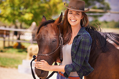 Buy stock photo Portrait of a young cowgirl standing outside with her horse