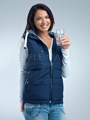 Buy stock photo A studio portrait of a beautiful woman standing and holding a glass of water