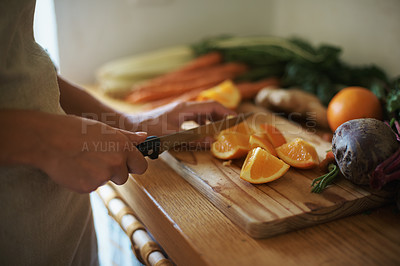 Buy stock photo Cropped shot of a woman slicing oranges on a chopping board