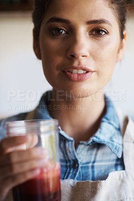 Buy stock photo A cropped portrait of a beautiful young woman holding a glass of freshly-squeezed juice