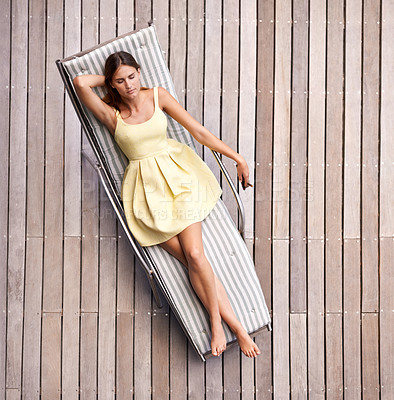 Buy stock photo A young, wealthy woman lying on her sunbed in a summer dress