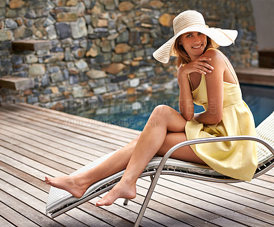 Buy stock photo An attractive woman wearing a sun hat while relaxing near a pool