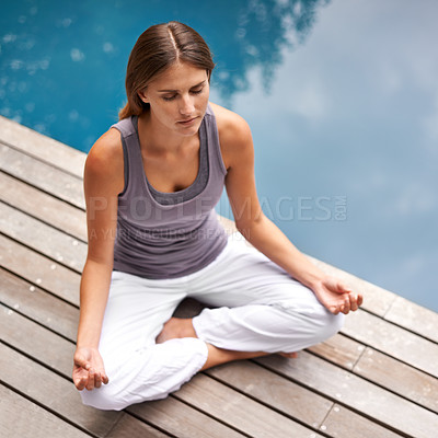 Buy stock photo Young woman meditating at the pool