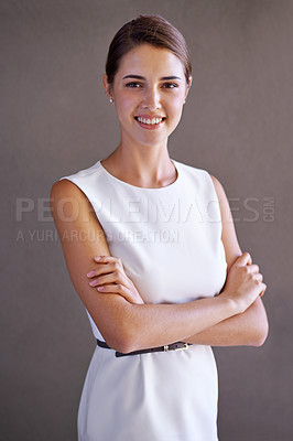 Buy stock photo Studio shot of a beautiful young woman crossing her arms
