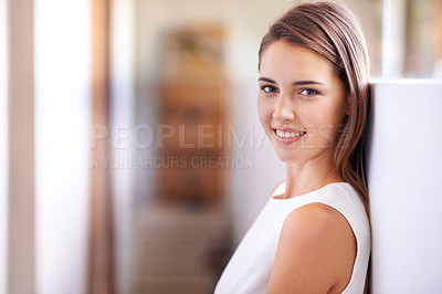 Buy stock photo Cropped portrait of a young woman leaning against a wall