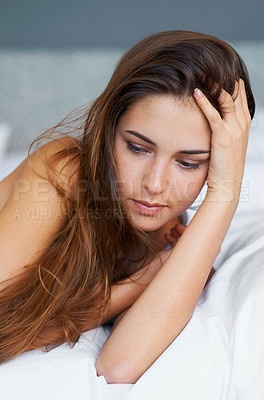 Buy stock photo A beautiful young woman lying on her bed looking thoughtful