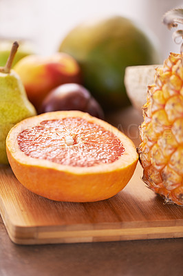 Buy stock photo A cropped shot of different fruits around a wooden chopping board