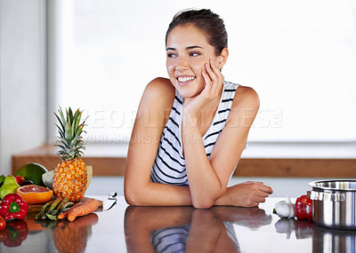 Buy stock photo A beautiful young woman leaning on her kitchen counter next to food and a cooking pot