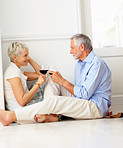 Mature couple enjoying a glass of wine at their home