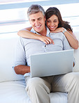 Beautiful happy smiling couple sitting together and working on the laptop