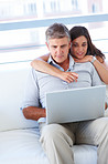 Young adult couple sitting on a sofa and surfing on laptop