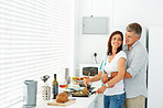 Happy mature man with his arms around his wife while she is cooking