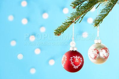 Buy stock photo Christmas decorations hanging from a tree branch, isolated on blue with scattered light effect - copyspace