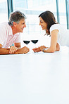 Happy mature couple lying down on the floor at home and having a glass of wine