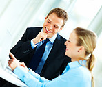 Business man and woman in a meeting using laptop