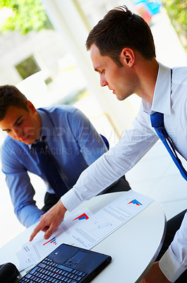Buy stock photo Shot of a two businessmen looking over documents together