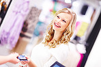 Attractive young woman making her shopping payment with a credit card