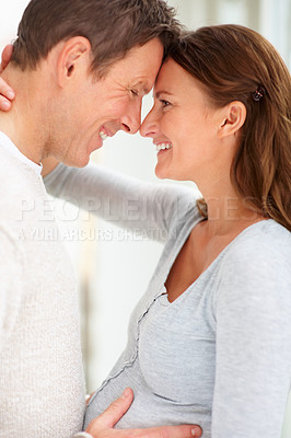 Excited young man holding his pregnant wife\'s belly