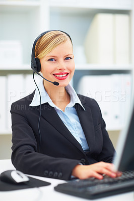 Portrait of young businesswoman working on computer and using headphones