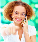 Business woman using a mobile phone pointing at you
