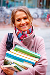 Young smiling woman with backpack holding books