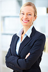 Confident young blond businesswoman standing with crossed arms
