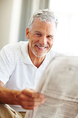 Buy stock photo Handsome senior man reading a newspaper