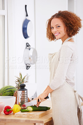 Happy young lady preparing food in the kitchen